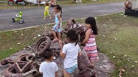 小孩們在一座壞塑像組合上玩耍。