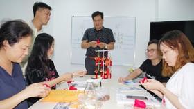 陳志明校長(中)正在指引學員製作粽子香囊。