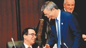在日本福岡召開的G20財長和央行行長會議上,大陸人民銀行行長易綱(右)與美國財政部長穆努欽(左)握手。(圖源:路透社)