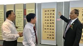 馮利發(左二)與林漢城(左一)陪同柬埔寨教育部國務秘書麥砂綸參觀越南區書法。