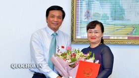 國會秘書長、國會辦公廳主任阮幸福(左)向范翠征同志(右)頒發國會常務委員會第705號《決議》並贈送鮮花祝賀。(圖源:Quochoi.vn)