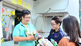來自同奈省的年輕人把生態磚塊成品交給 武仲廷副書記(左)。