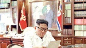 金正恩坐在桌前閱讀特朗普的親筆信。(圖源:KCNA)