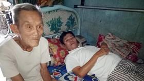 楊蝦伯伯與癱瘓在床的長子錦雄。