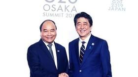政府總理阮春福(左)與日本首相安倍晉三握手。(圖源:越通社)