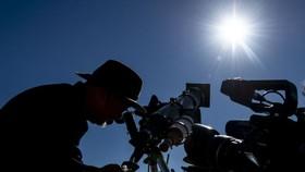 當地時間7月1日,智利聖地亞哥以北的阿塔卡馬沙漠一處天文營地的入口處,遊客帶著特制的眼鏡嘗試觀看日食。(圖源:AFP)