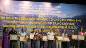 市各友好組織聯合會副主席阮氏紅艷(左一)向有重大貢獻的組織頒發市人委會獎狀。(圖源:明榮)
