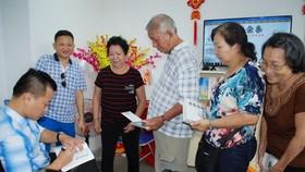 作者麒麟(左一)給華人讀者簽名贈書。