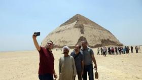 7月13日,人們在埃及首都開羅以南的彎曲金字塔前拍照。(圖源:新華社)