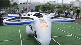 """日本NEC公司向媒體公開了搭載人和物體在空中移動的""""空中飛行汽車""""樣機的懸浮試驗。(圖源:AP)"""