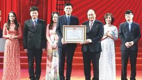 政府總理阮春福(前右)向《勞動報》總編輯阮玉顯頒授三等勞動勳章。(圖源:越通社)