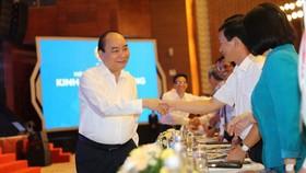 政府總理阮春福(左)同與會代表親切握手,互致問候。(圖源:PV)