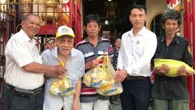立案會長王奕謀(左一)與代表向窮人送禮物。