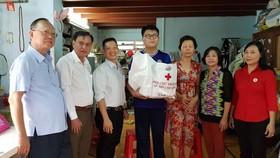 (左起)盧耀南理事長、陳長山主席、林曉東理事贈送禮物給貧困學生黎元魁。