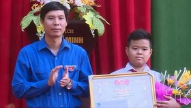 拾遺不昧的七年級A班學生阮平明(右)獲頒發該省共青團執委會的獎狀。(圖源:越通社)