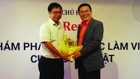 第五郡企業協會副主席、華人企業家周先識(右)送花感謝贊助單位。