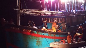 Các nhân viên cứu nạn đưa ngư dân Huỳnh Văn Cương sang tàu cứu nạn bằng xuồng cao su