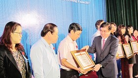 Chairman of the HCMC People's Committee Nguyen Thanh Phong gives certificates of merit to individuals and organizations well performing tax obligations on August 3 (Photo: SGGP)