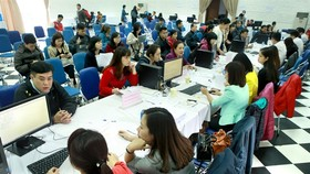 Tax officials (on the right side of the tables) receive personal income tax finalisation documents from Hanoi residents. The Vietnamese Government aims to considerably increase the number of administrative procedures processed via electronic systems in th