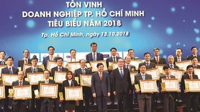 HCMC Party leader Nguyen Thien Nhan and chairman of HCMC People's Committee Nguyen Thanh Phong congratulates oustanding businesses 2018 in HCMC on October 13 (Photo: SGGP)