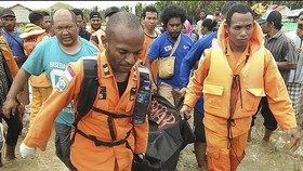 Rescuers carry the body of a flood victim (Photo: VNA)
