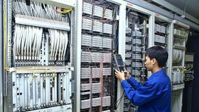 A technician checks telecoms equipment at the Telecommunication Center of Vietnam Posts and Telecommunications Group (VNPT) in the northern province of Lai Chau. (Photo: VNA/VNS)