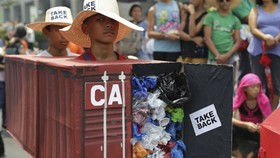Filipino environmental activists wear a mock container vans filled with garbage to symbolize the 50 containers of waste that were shipped from Canada to the Philippines two years ago as they hold a protest outside the Canadian Embassy in the financial dis