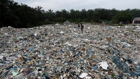 People walk through plastic waste piled outside an illegal recycling factory in Jenjarom in Kuala Langat district, Malaysia. (Photo: Reuters)