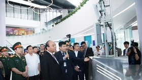 Prime Minister Nguyen Xuan Phuc sees new technology products of Vietttel at the event (Photo: SGGP)