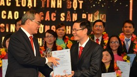 Secretary Nguyen Thien Nhan (L) gives the awards to the work 'Study of the technological process of producing high resistant starches and low-sugar food produ from Vietnam's foods cts for obese and diabetic patients' (Photo: SGGP)