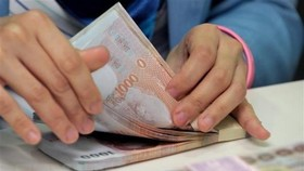 The baht notes are counted at the Krungthai Bank in Bangkok (Illustrative image. Photo: AFP/VNA)