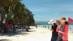 Tourists on a Philippine beach (Source: https://www.pna.gov.ph)