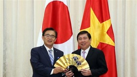 Chairman of HCM City People's committee Nguyen Thanh Phong (R) receives a souvenir from Governor of Japan's Aichi prefecture Hideaki Ohmura (Photo: VNA)