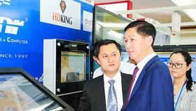 Phó Chủ tịch UBND TPHCMTrần Vĩnh Tuyến (giữa)tham quan gian hàng trưng bày của Công ty Điện tử Cây Tre Việt