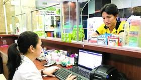Nhân viên một nhà thuốc ở quận 7, TPHCM, truy cập dữ liệu thuốc qua mạng.  Ảnh: Hoàng Hùng