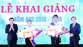 Chủ tịch UBND TPHCM Nguyễn Thành Phong (trái) trao học bổng tặng sinh viên