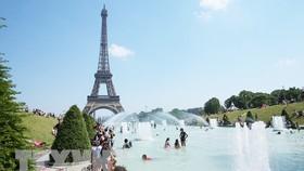 Người dân tránh nắng nóng bên vòi phun nước ở Paris, Pháp. Ảnh: TTXVN