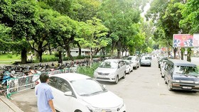 Ô tô đậu trên vỉa hè công viên Lê Văn Tám phía đường Hai Bà Trưng. Ảnh: THÀNH TRÍ