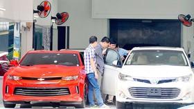 Xem ô tô nhập khẩu tại một salon ở TPHCM. Ảnh: CAO THĂNG