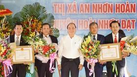 Thủ tướng Nguyễn Xuân Phúc trao quyết định cho thị xã An Nhơn và huyện Hoài Nhơn. Ảnh: VGP/Quang Hiếu
