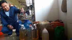 Người dân sử dụng que củi nhúng vào nước giếng nhiễm dầu và châm lửa đốt