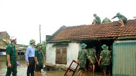 Lực lượng chức năng giúp người dân lợp lại mái nhà sau lốc xoáy ở xã Xuân Phổ, huyện Nghi Xuân, tỉnh Hà Tĩnh