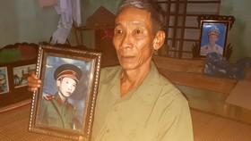 Ông Phạm Văn Bình bên hình ảnh ông chụp thời đi bộ đội