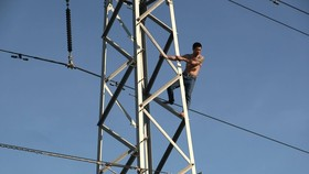 Nam thanh niên xăm trổ có biểu hiện ngáo đá vừa nhún nhảy, la hét trên cột điện cao thế
