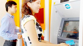 Khách hàng sử dụng thẻ ATM ngân hàng        Ảnh: THÀNH TRÍ