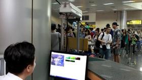 Sử dụng máy đo thân nhiệt tia hồng ngoại nhằm kiểm soát dịch bệnh ở sân bay Nội Bài. Ảnh: TTXVN