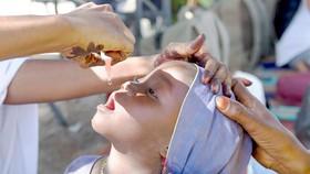 Cho trẻ uống vaccine ngừa bại liệt ở châu Phi