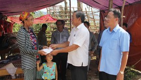 Đoàn công tác trao tiền hỗ trợ gia đình bà Đoàn Tiến Lực, thôn Minh Cẩm Ngoại, xã Phong Hóa, huyện Tuyên Hóa dựng lại nhà bị sập. Ảnh: HOÀI NAM