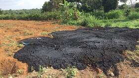 Chất thải đen sì được một nhà máy chở đến đổ tại bãi đất trống gần nhà một hộ dân cạnh khu công nghiệp