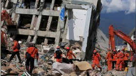 Lực lượng cứu hộ đang nỗ lực tìm kiếm những người  được cho là mắc kẹt trong đống đổ nát. Ảnh: Reuters
